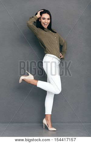 Cheerful beauty. Full lenght of attractive young woman in smart casual wear posing against grey background and looking happy