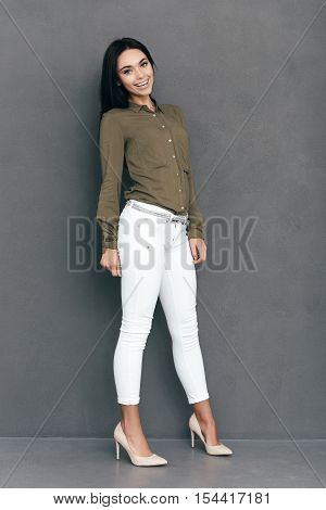 Young and so beautiful. Full lenght of attractive young woman in smart casual wear posing against grey background and looking happy