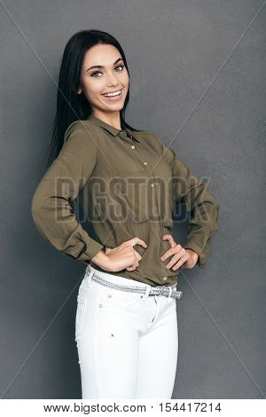 Young and beautiful. Happy young woman in smart casual wear standing against grey background and holding hands on hip