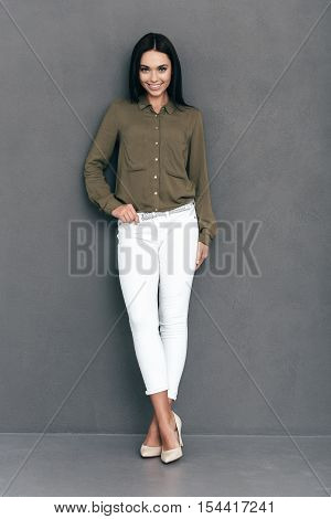 Confident and beautiful. Full length of attractive young woman in smart casual wear standing against grey background and smiling