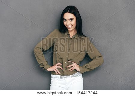 Confident in her look. Happy young woman in smart casual wear standing against grey background and holding hands on hip