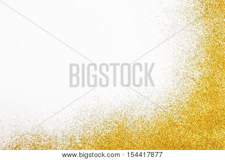Golden glitter sand texture frame on white, abstract background with copy space. Yellow dusty shimmer decoration border, shiny and sparkling. Holidays and glamour concept.