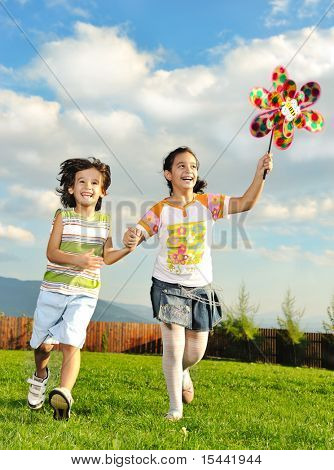 Fantastic scene of happy children running and playing care freely on green meadow in nature