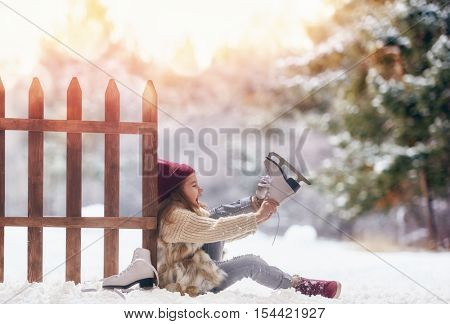 Happy child playing on a winter walk in nature. Cute little kid girl is going skate outdoors.