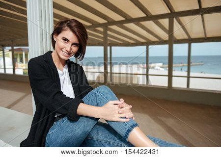 Portrait of smiling beautiful young woman sitting in arbour on the seaside