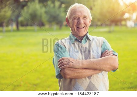 Senior man laughing. Person with crossed arms outdoor. The sense of joke. Wittiness and humor.
