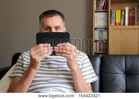 Serious Stern Man Watching From Over A Tablet Computer