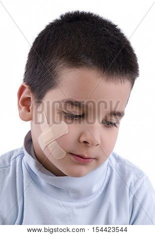 Band aid applied to cute boy's cheek isolated on white background.
