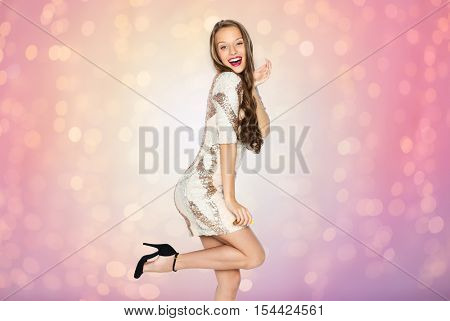 people, style, holidays, hairstyle and fashion concept - happy young woman or teen girl in fancy dress with sequins and long wavy hair posing over rose quartz and serenity lights background