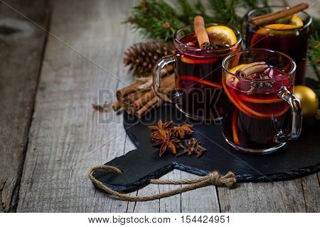 Mulled wine in glass cups with spices and decorations
