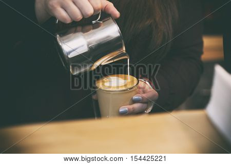 Young woman makes a latte art