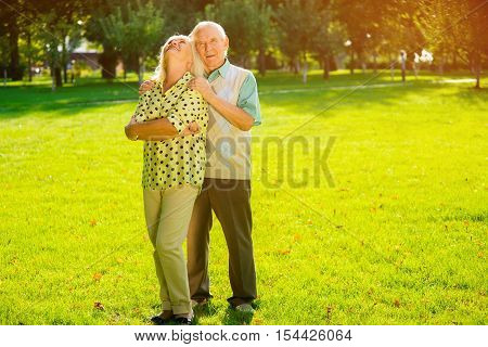 Old couple outdoors. Woman smiling and looking up. Warmth and tenderness. You are my destiny.