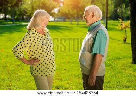 Elderly man and woman outdoors. Smiling lady looks at man. Let's make this day special. Invitation for a dinner.