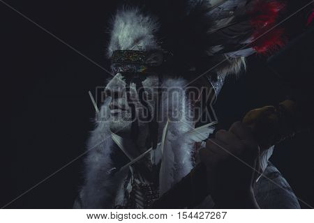 West, American Indian chief with feather headdress and traditional war ax