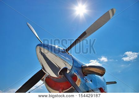 Turboprop plane engine and propeller closeup view against the sun in the blue sky