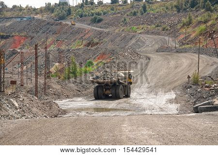 View to the iron ore opencast with dump truck transporting the ore from the quarry