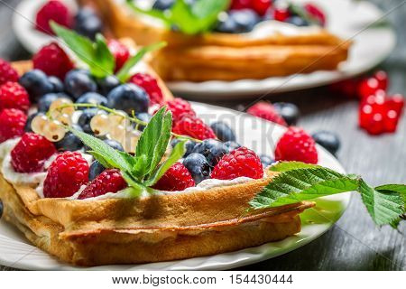 Waffels with cream blueberry and raspberry on wooden table