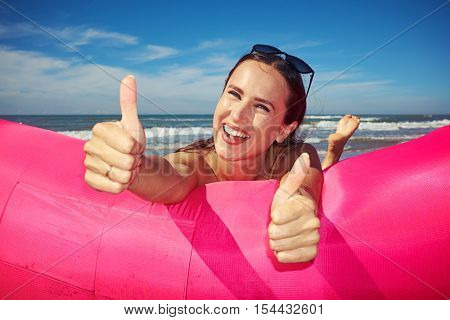 Close-up of joyful and laughing softly woman is lying on stomach on pink inflatable boat and giving thumbs up. Happy smiling woman in lovely striped beachwear is full of positive emotions