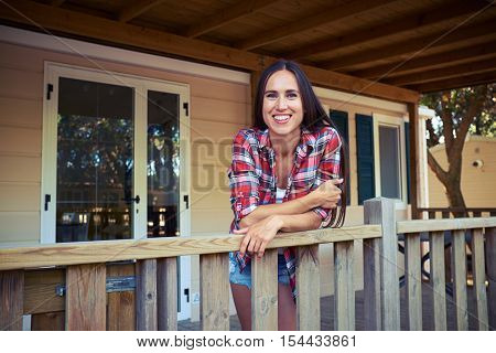 Mid shot of joyful and laughing softly brunette posing at the camera while standing on the porch of the wooden rest house. She leans on the handrail and looks at the camera