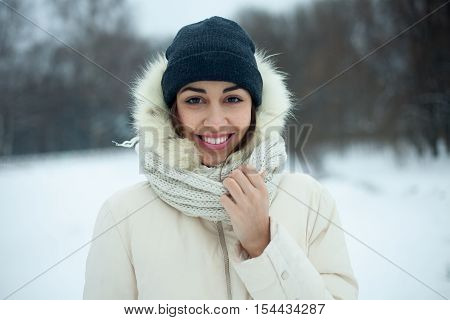Christmas girl outdoor portrait. Winter woman blowing snow in a park. Flying Snowflakes. Sunny day. Backlit. Beauty young woman Having Fun in Winter Park. Good mood