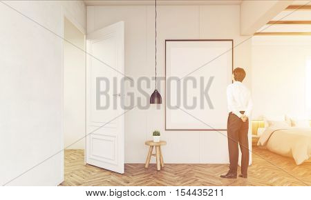 Rear view of businessman standing in his bedroom and looking at blank framed poster on the wall. Concept of home decoration. Mock up. Toned image. 3d rendering