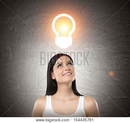 Close up of smiling woman in white tank top standing under light bulb sketch on blackboard. Concept of bright idea