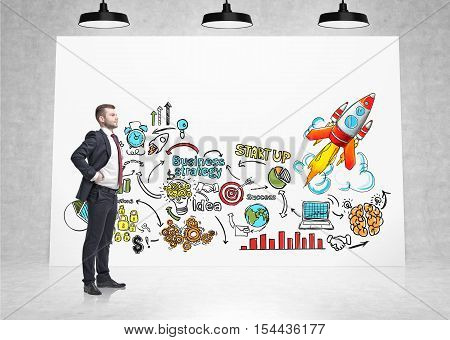 Side view of confident businessman looking at colorful startup sketch on horizontal poster in concrete room. Concept of project launching