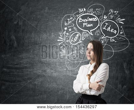 Side view of a girl with braided hair standing near chalkboard with business plan sketch on it. Concept of strategy development. Mock up