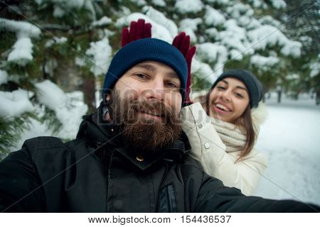 Happy couple making selfie photo outdoors. closeup of a caucasian and loving couple is doing selfie on smartphone. lifestyle people and outdoor concept and idea