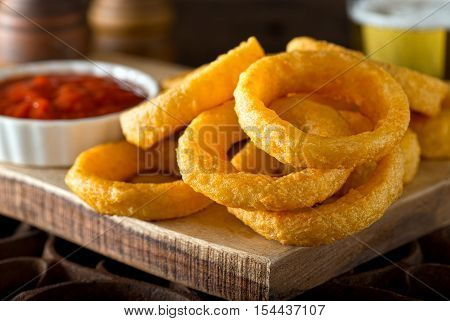 Delicious pub style onion rings with ketchup and beer.