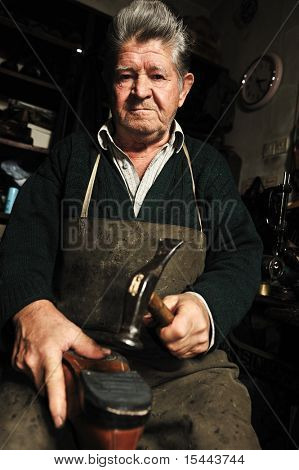 Elderly man in his workshop repairing a shoe with a hammer