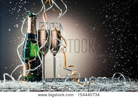 Bottle, two champagne wineglasses with silver and golden ribbons, snowfall