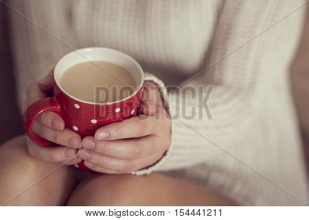 Close up of woman's hands holding a cup of coffee wearing a white sweater and enjoying the leisure time