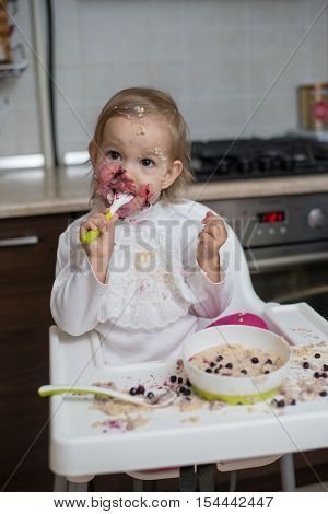 Cute dirty little girl eating healthy porridge with bilberry with plastic spoon while sitting in the high chair at table in the kitchen. Image with selective focus.