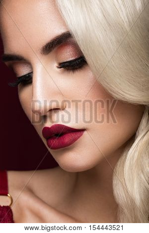Beautiful blonde in a Hollywood manner with curls, red lips, red lingerie. Beauty face and hair. Picture taken in the studio