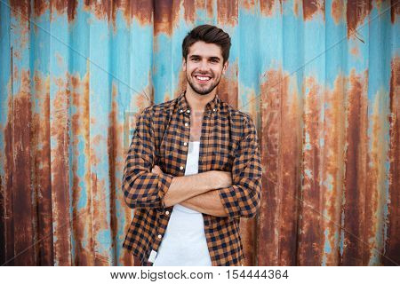 Happy young man in plaid shirt standing with arms crossed over blue metal background with rust