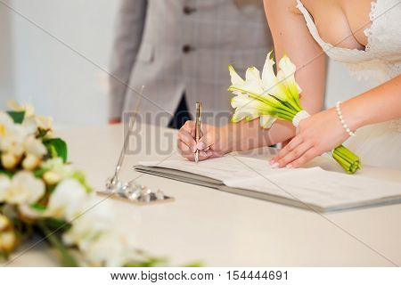 Bride hand with a pen signing wedding license. Marriage contract.