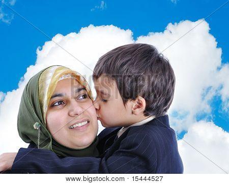 Muslim woman kissing her son