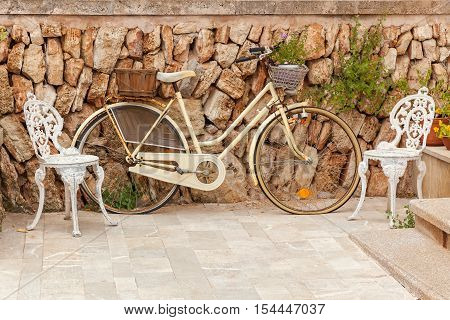 Vintage bike. Vintage bike outdoors with flowers two stylish chairs near the brick wall.