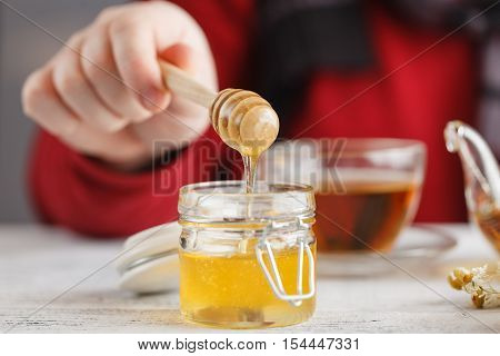 Man Hold Cup Of Hot Tea In Glass Cup, Jar Of Honey, Honey Dipper On The Old Wooden Background