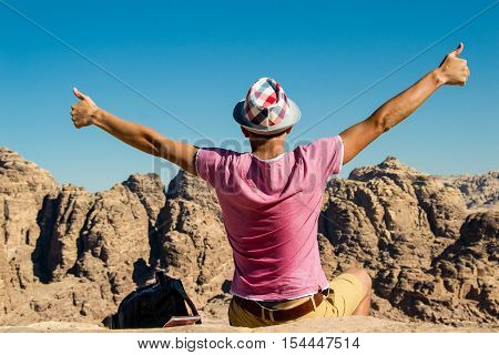 Photo of the Self-satisfied man in hat on top mountain with thumbs up. Do not give up motivation concept. Happy hiker winning reaching life goal success freedom and achievement.