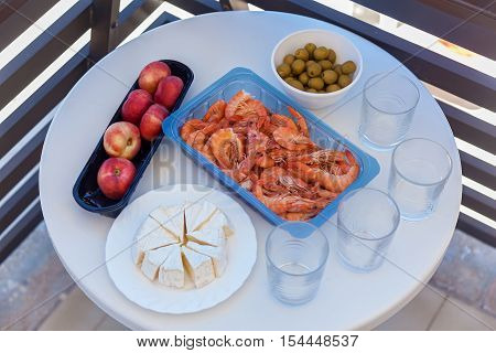 Food on the table. Big prawns olives peaches and white cake are laying on the plates with four glasses on the white table.