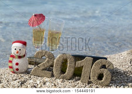 Champagne bottle lying on the beach with two champagne glasses snowman and cardboard numbers 2016 placed next to it. Seascape in the background.