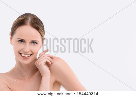 My skin is perfect. Joyful young woman is touching her shoulder with gentleness. She is standing and smiling. Isolated and copy space in right side