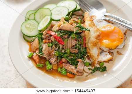 Pork with chili & Basil leaves topping with fried egg on plate.