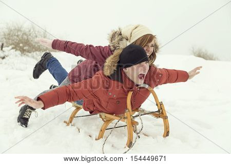 Young couple lying on a sleigh rushing down the hill enjoying winter holidays