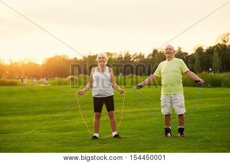 Couple with skipping ropes. Senior people on meadow. Test your endurance. Aerobic trainings for pensioners.