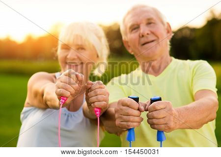 Elderly couple outdoors. Hands holding skipping ropes. Focus and work on result. Be faster and stronger.