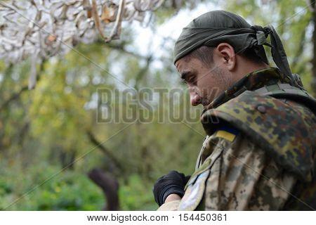 Ukrainian soldier looks down sadly. Ukraine, Lugansk region, 7 October 2016. The war in Ukraine.