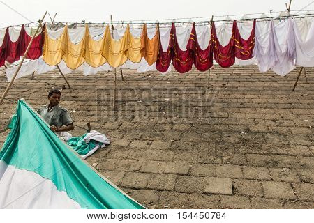 DHAKA BANGLADESH- MARCH 01 2016. Unidentified washerman dry his cloth in on the dam